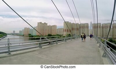 People walk on a pedestrian bridge