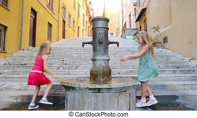 Adorable girls drinking water from street fountain at hot summer day in Rome, Italy