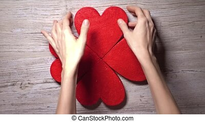 Girl taking four red hearts from a wooden table, top view....