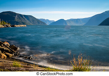 smooth water at norwegian fjord - smooth and blue water at...