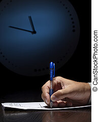 On the test - man doing written test with the clock in the...