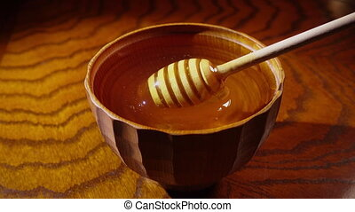 Honey in the wooden bowl with dipper - Honey dripping from a...