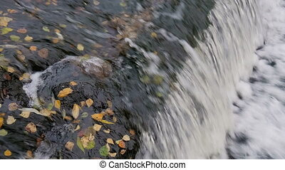 A small waterfall in the park in autumn. - A small waterfall...