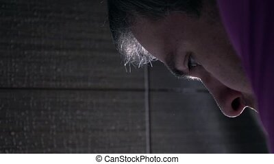 Young man washing his face in the bathroom, super slow...