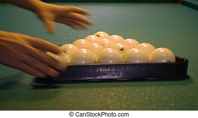 preparing to billiard game - man puts billiard balls on the...
