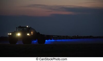 Tractor on the field sprinkles - Speeding tractor on the...