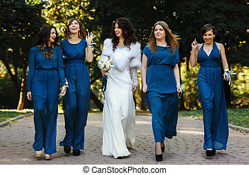 Bride and girls in blue walking around the park