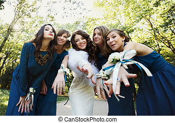 Bride with bridesmaid reaching out their hands and smiling