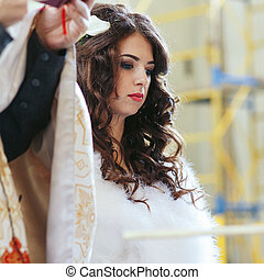 Bride standing thoughtful during the ceremony