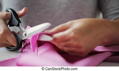 woman with tailor scissors cutting out fabric - people,...
