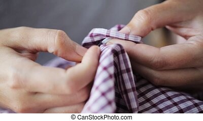 woman with needle stitching on button to shirt - people,...