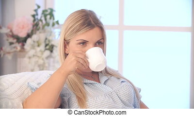 pregnant woman drinking tea while lying on bed at home