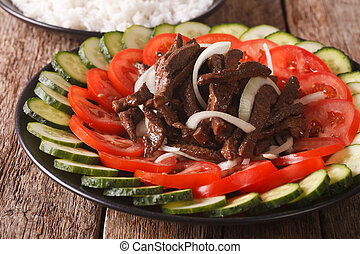 Cambodian beef Lok Lak with fresh vegetables close-up....