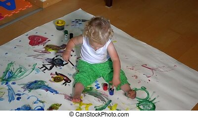 Funny little girl painting on floor at home. 4K