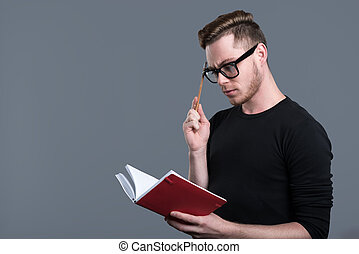Thoughtful young bearded man in glasses - Time to organize...