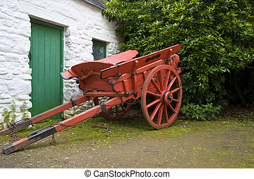 Old horse drawn cart beside whitewashed outbuilding