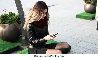 Woman using her smartphone - Young pretty woman in black...