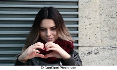 Young woman showing heart - Young pretty woman in black...