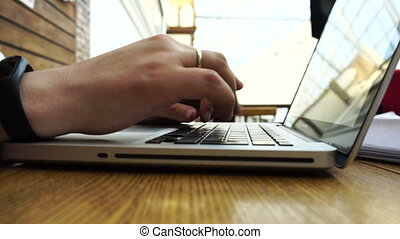 Young man with gold wedding ring using his laptop on the...