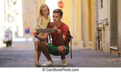 Adorable little girl and father with map of european city...
