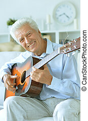 happy Senior man with guitar at home