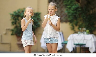 Little girls eating ice-cream outdoors at summer. Cute kids...