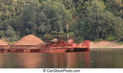 tugboat pushes a barge loaded with sand on the river