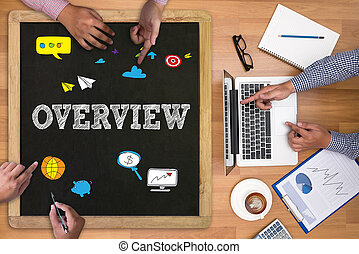 OVERVIEW Businessman working at office desk and using...