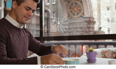 Man drinks coffee at the cafe - Brunette man drinking his...