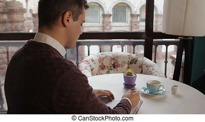 Man smells coffee at the cafe - Young man smelling his...