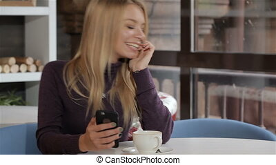 Woman messages by her cellphone at the cafe