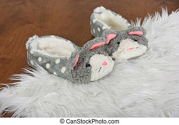fuzzy bunny slippers on white furry rug and wood floor