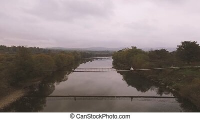 Aerial video. Loving Couple on a Wooden Bridge in the Mountains