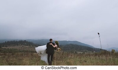 Groom Spining Around with his Wife in Hands