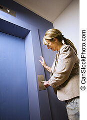 mature woman by the lift - Terrified woman waits on a blue...