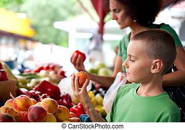 Cute boy at the farmer\'s market - Cute boy with his mother...