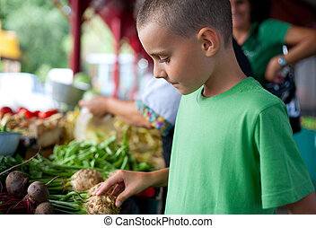 Cute boy buying vegetables - Cute boy with his mother buying...