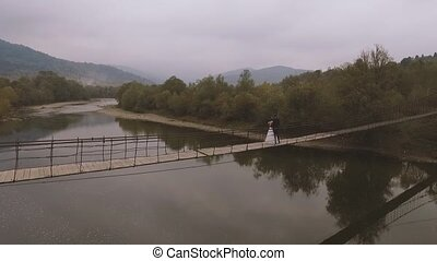 Loving Couple on a Wooden Bridge in the Mountains. Aerial...