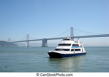 Alameda Oakland Ferry passes under the Bay Bridge. Sail boat...