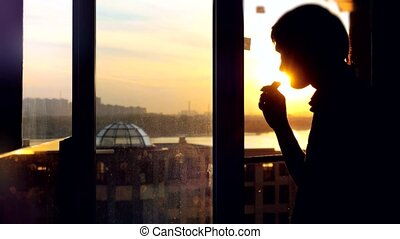Back view of young man sitting on window with coffee cup, has a breakfast, looking at dawn city scenery. Handsome casual guy relaxing and watching sunrise.