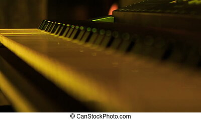 Closeup Electric Piano Keys under Flashes of Colourful...