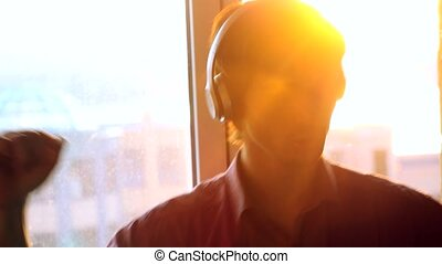 Young handsome man listening to music from a smart phone with headphones on the sunset city background.