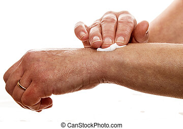 senior woman rubbing her wrist with a pain relieving cream -...