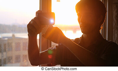 Young businessman taking picture with mobile phone against panoramic window  sunset view