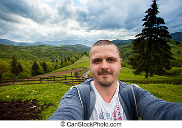 Young man is standing on the hill and taking photo of...