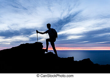 Man hiking silhouette in mountains, ocean and sunset inspirational landscape
