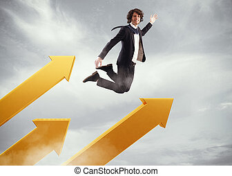 Go over to success - Businessman jumps on big arrows in the...