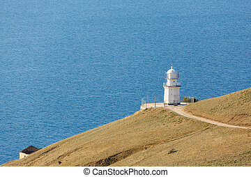 white lighthouse on the background of the sea