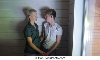 Smiling gay couple hugging and kissing at home - Smiling gay...