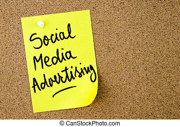 Social Media Advertising text written on yellow paper note...